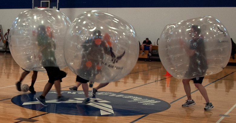 A group of Airmen collide during the start of a bubble soccer game April 22, 2016, during a tournament inside the Freedom Hall Fitness Center on F.E. Warren Air Force Base, Wyo. Teamwork was key as teams tried to score goals while remaining upright. (U.S. Air Force photo by Senior Airman Brandon Valle)