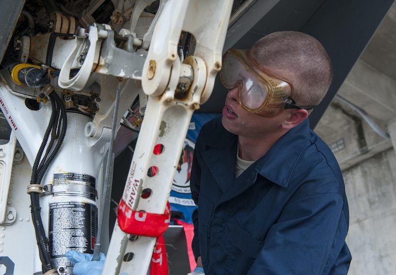 U.S. Air Force Airman 1st Class Brandon Meyer, 44th Aircraft Maintenance Unit crew chief, uses an aircraft lubricant to ensure all moving parts are operational at all times, April 26, 2016, at Kadena Air Base Japan. This maintenance is performed every thirty days when the F-15C Eagles are washed. (U.S. Air Force photo by Airman Zackary A. Henry)