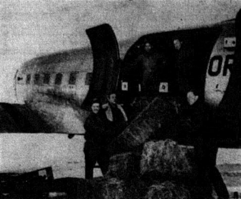 Haylift team members are shown loading hay aboard an OreANG C-47 at La Grande Airport in preparation for the 1 February 1949 mission.  Left to right:  District Game Agent Austin F. Hamer, Lt. Richard J. Schmidt, SSgt Chester Strauch, SSgt Verl Ward and Mr. John McKean, State Game Division Chief of Upland Game.  (Photo by Frank Schiro, courtesy La Grande Observer, via Eastern Oregon University Library)