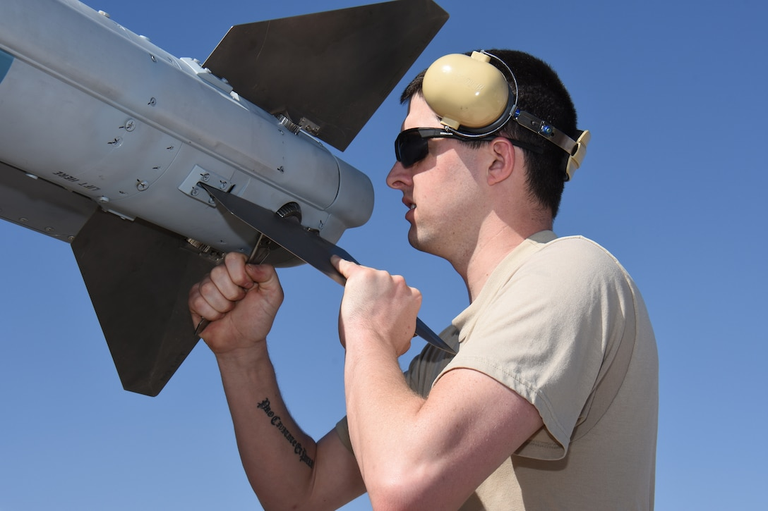 Senior Airman Elliot Snow, aircraft maintenance specialist with the 115th Fighter Wing in Madison, Wis. adjusts the fins of an AIM-120 Advanced Medium-Range Air-to-Air Missile (AMRAAM) at Nellis Air Force Base, Nev. April 5, 2016. The Wisconsin Air National Guard unit deployed more than 100 Airmen and eight F-16 Fighting Falcons for two weeks to support advanced training in weapons and tactics employment at the United States Air Force Weapons School. (U.S. Air National Guard photo by Master Sgt. Paul Gorman/Released)