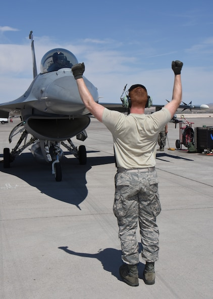 Airman 1st Class Nathan Moll, aircraft maintenance specialist with the 115th Fighter Wing in Madison, Wis., marshals an F-16 Fighting Falcon on the aircraft ramp at Nellis Air Force Base, Nev., April 4, 2016. The Wisconsin Air National Guard unit deployed more than 100 Airmen and eight F-16 Fighting Falcons for two weeks to support advanced training in weapons and tactics employment at the United States Air Force Weapons School. (U.S. Air National Guard photo by Master Sgt. Paul Gorman/Released)