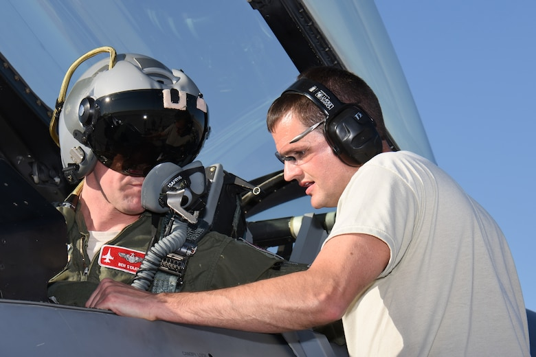 Master Sgt. Michael Lincoln, aircrew egress systems specialist for the 115th Fighter Wing in Madison, Wis., addresses canopy closure issues with Maj. Benjamin Staats, 115 FW pilot, on the aircraft ramp at Nellis Air Force Base, Nev., April 4, 2016. The Wisconsin Air National Guard unit deployed more than 100 Airmen and eight F-16 Fighting Falcons for two weeks to support advanced training in weapons and tactics employment at the United States Air Force Weapons School. (U.S. Air National Guard photo by Master Sgt. Paul Gorman/Released)