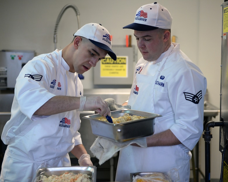 Senior Airman Caleb D. Cejka and Senior Airman Ryan A. Ducharme of the 157th Force Support Squadron's Sustainment Services Flight prepare food during the unit training assembly, April 2, 2016. (U.S. Air National Guard photo by Staff Sgt. Curtis J. Lenz)