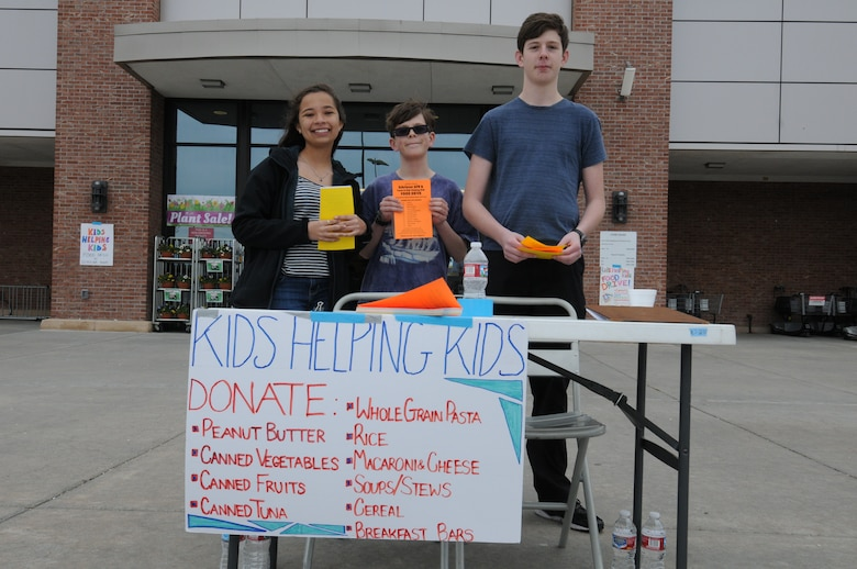 Mikayla Mobley, and Thomas and Spencer Doran inform shoppers about Kids Helping Kids at the commissary on Peterson Air Force Base, Colorado, Saturday, April 23, 2016. Schriever families held the drive for the Ellicott Helping Hands Food Pantry. (U.S. Air Force photo/2nd Lt. Darren Domingo)