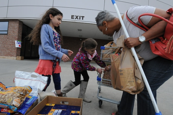 Alaina and Abrielle Janaros gather donations from Valerie Decoursey during a Kids Helping Kids donation event at the commissary on Peterson Air Force Base, Colorado, Saturday, April 23, 2016. Schriever families held the drive for the Ellicott Helping Hands Food Pantry. (U.S. Air Force photo/2nd Lt. Darren Domingo)