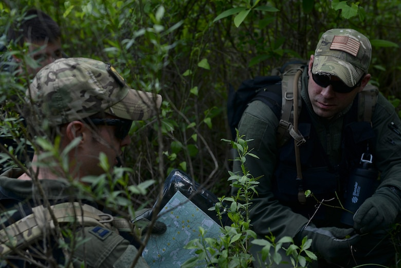 From left, U.S. Air Force Capt. Jon Clausen, 61st Airlift Squadron C-130J pilot, and U.S. Air Force Staff Sgt. Matthew Morgridge, 61st Airlift Squadron C-130J loadmaster, review a topographic map April 22, 2016, near Ft. Polk, La. Clausen and Morgridge, along with other aircrew members, used various methods without any radio transmission to be recovered during Green Flag 16-06. (U.S. Air Force photo by Airman 1st Class Mercedes Taylor)