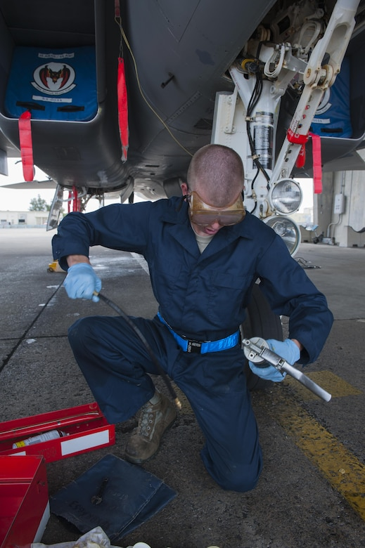 U.S. Air Force Brandon Meyer, 44th Aircraft Maintenance Unit crew chief, sets up a lubricant pressure gun for applying lubricant to the moving parts and bearings of the aircraft to minimize any down time, April 26, 2016, at Kadena Air Base Japan. Each F-15C Eagle must be lubricated after each monthly cleaning, which removes most of the lubricant. (U.S. Air Force photo by Airman Zackary A. Henry)