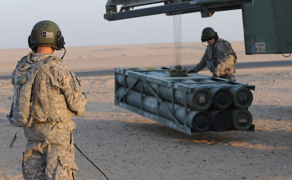 Staff Sgt. Jonathon Hoffnauer, High Mobility Artillery Rocket System (HiMARS) Crew Chief, and Spc. Mario Ybarra, HiMARS Gunner, load a rocket pod onto a M142 High Mobility Artillery Rocket System (HiMARS).  (U.S. Army photo by Staff Sgt. Noel Gerig)