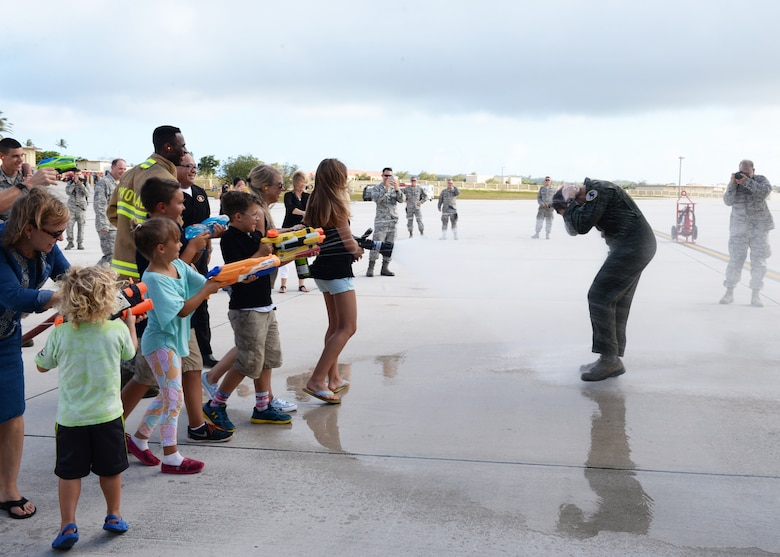 Brig. Gen. Andrew Toth, 36th Wing commander, is sprayed with water by friends and family after landing a B-52 Stratofortress during a fini-flight April 26, 2016, at Andersen Air Force Base, Guam. The fini-flight, which is a tradition carried throughout the Air Force, marks Toth's final flight on Guam. (U.S. Air Force photo by Senior Airman Cierra Presentado)