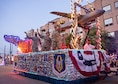 Airmen from the 433rd Airlift Wing wave to the crowd as they  participate in the Fiesta Flambeau parade April 23, 2016. The Fiesta Flambeau parade is one of the largest illuminated parades in the world, with over 750,000 spectators and 1.5 million television viewers. (U.S. Air Force photo by Benjamin Faske) (released)