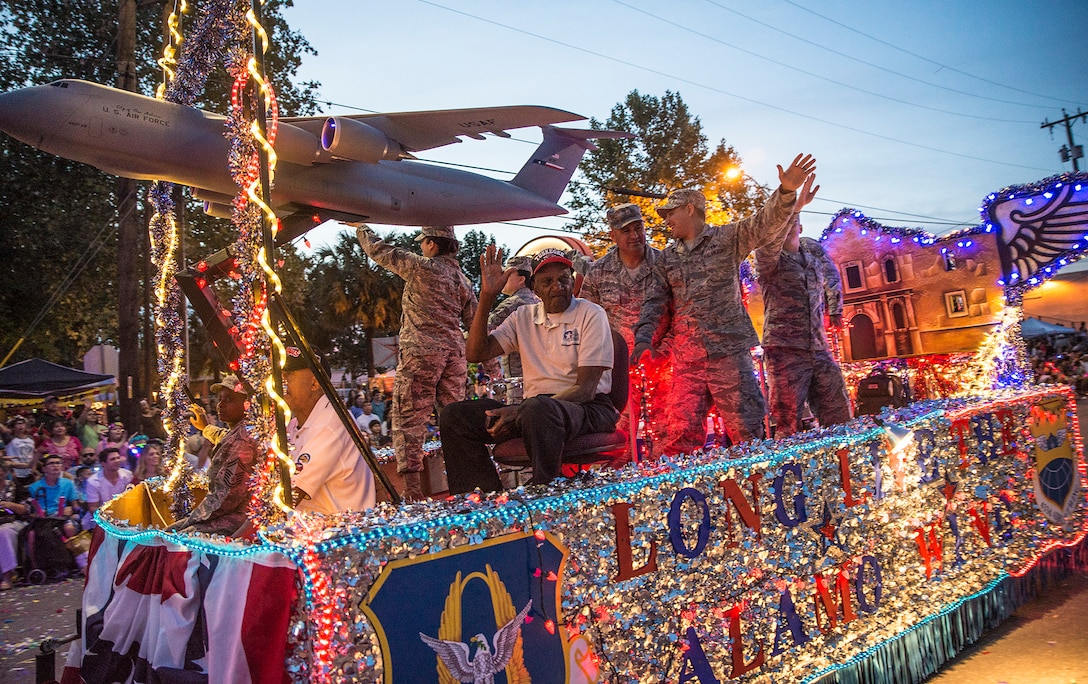Theodore Johnson, a documented original Tuskegee Airman and San Antonio resident, waves to the crowd while riding on the 433rd Airlift Wing float during the Fiesta Flambeau parade April 23, 2016. (U.S. Air Force photo by Benjamin Faske) (released)