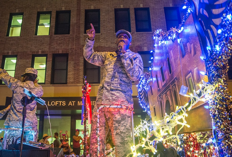 Tech. Sgt. Robert Carter, 531st Intelligence Squadron section chief knowledge operations, sings to the crowd as the 433rd Airlift Wing float during the Fiesta Flambeau parade April 23, 2016. The Fiesta Flambeau parade is one of the largest illuminated parades in the world, with over 750,000 spectators and 1.5 million television viewers. (U.S. Air Force photo by Benjamin Faske) (released)