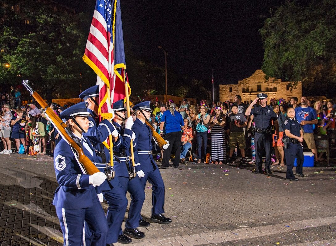 The 433rd Airlift Wing Honor Guard marches past the Alamo during the Fiesta Flambeau parade April 23, 2016. The Fiesta Flambeau parade is one of the largest illuminated parades in the world, with over 750,000 spectators and 1.5 million television viewers.  (U.S. Air Force photo by Benjamin Faske) (released)
