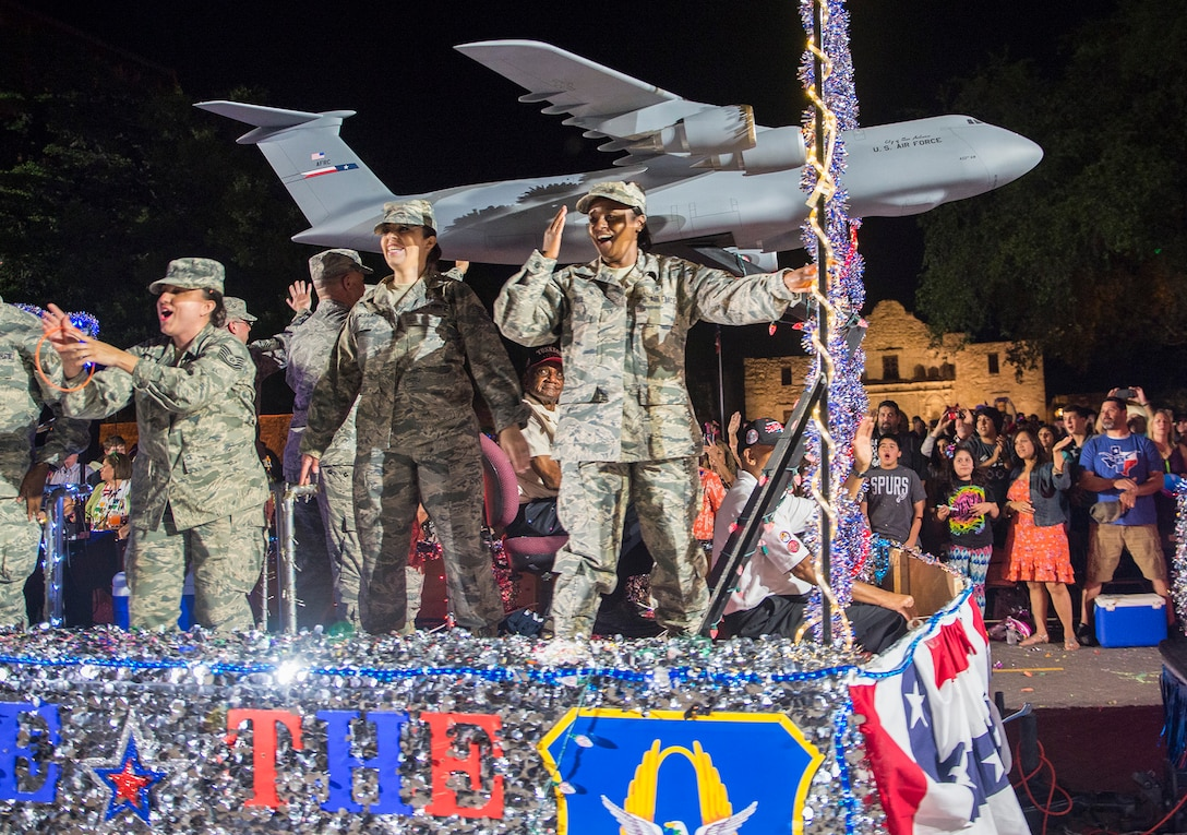 Airmen with the 433rd Airlift Wing wave to the grandstands as they pass in front of the Alamo during the Fiesta Flambeau parade April 23, 2016. The Fiesta Flambeau parade is one of the largest illuminated parades in the world, with over 750,000 spectators and 1.5 million television viewers.  (U.S. Air Force photo by Benjamin Faske) (released)