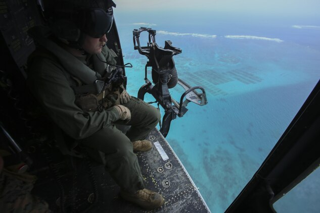 Sgt. Jeffrey L. Allen scopes out the terrain from his seat in a UH-1Y Huey, April 8, 2016, at Marine Corps Air Station Futenma, Okinawa, Japan. Allen, along with other crew chiefs and aircraft maintainers, may work up to 16 hours a day performing maintenance and checks on aircraft to ensure safe missions. Allen, from Ennis, Texas, is with Marine Light Attack Helicopter Squadron 167, currently supporting Marine Aircraft Group 36, 1st Marine Aircraft Wing, III Marine Expeditionary Force, under the unit deployment program.
