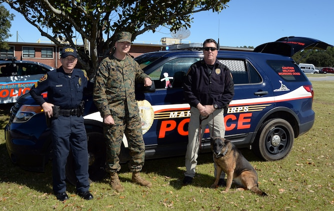 """Staff Sgt. Paul Delekto (center), services chief, Marine Corps Police Department, Marine Corps Logistics Base Albany, poses with """"Flat Stanley"""" during a recent photo shoot. Flat Stanley experienced what it was like to be a military police officer aboard a Marine Corps installation."""