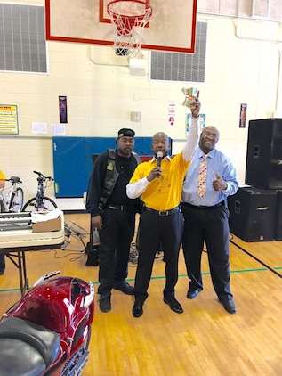 Several Marine Corps Logistics Base Albany civilian-Marines as well as contractors join more than a dozen area bikers from several motorcycle clubs and organizations at West Town Elementary School, Albany, Georgia, for a pep rally, recently. Principal Steven Dudley (center) and other school personnel invited motorcyclists to the event to entertain, educate and motivate students. The roughly 20 bikers suited up in their traditional riders gear to participate in the celebration, which was organized to reward the students for their success in raising their reading scores by more100 points.