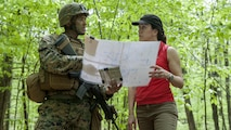 Under Secretary of the Navy Dr. Janine Davidson receives a brief from 2nd Lt. Scott R. Pierce, a student at The Basic School, on his platoon's defensive position in a training area at Marine Corps Base Quantico, Virginia, April 26, 2016. Davidson met with Marine Corps Combat Development Command leadership and Marines at TBS to better understand how the service trains, educates and equips its force.