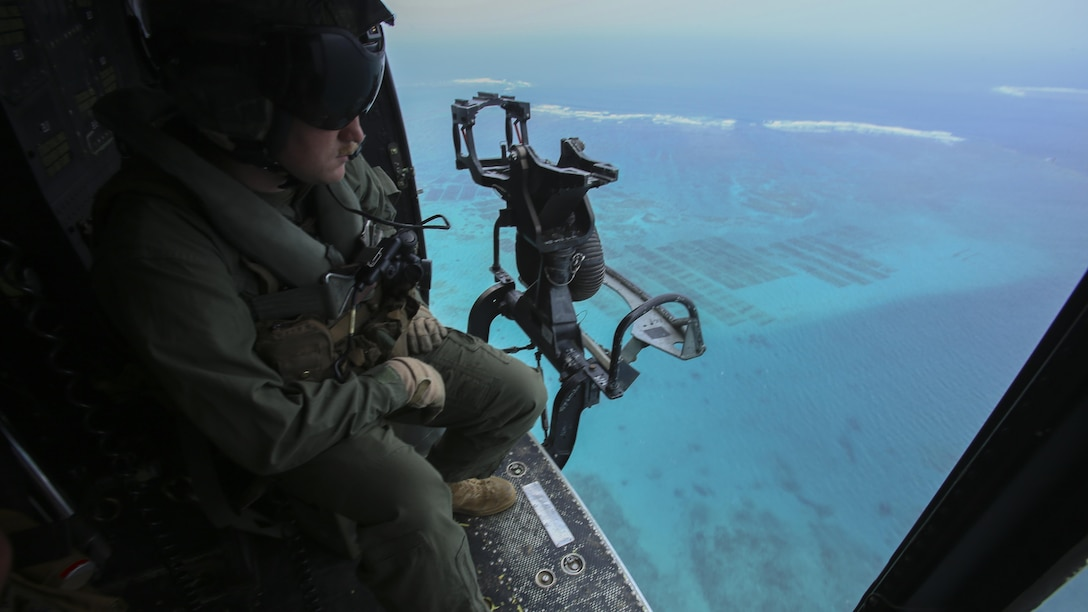 Sgt. Jeffrey L. Allen scopes out the terrain from his seat in a UH-1Y Huey at Marine Corps Air Station Futenma, Okinawa, Japan, April 8, 2016,. Allen, along with other crew chiefs and aircraft maintainers, may work up to 16 hours a day performing maintenance and checks on aircraft to ensure safe missions. Allen, from Ennis, Texas, is with Marine Light Attack Helicopter Squadron 167, currently supporting Marine Aircraft Group 36, 1st Marine Aircraft Wing, III Marine Expeditionary Force, under the unit deployment program.