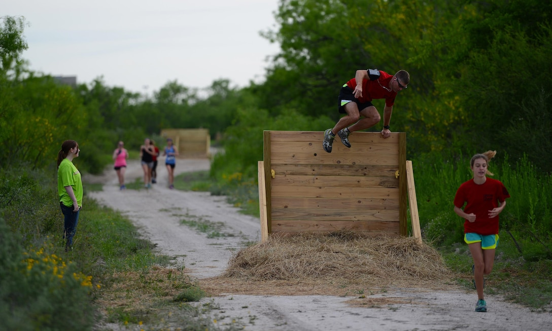 Lt. Col. Gregory Soderstrom, 47th Student Squadron commander, second to right, climbs over an obstacle during the run portion at the Adventure Race on Laughlin Air Force Base, Texas, April 23, 2016. The Laughlin Adventure Race began in 2004 and has grown into a major event for the Del Rio and Laughlin communities. More than 5,000 people have competed in the race across Val Verde County. (U.S. Air Force photo by Senior Airman Ariel D. Partlow)