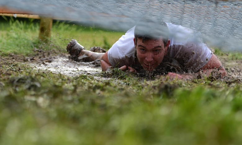 A competitor at the 12th Annual Adventure Race low crawls through an obstacle on Laughlin Air Force Base, Texas, April 23, 2016. The run portion of the race included mystery challenges along the route. (U.S. Air Force photo by Senior Airman Ariel D. Partlow)