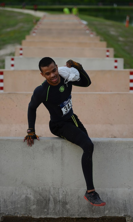 """Airman 1st Class Omari Thomas, 47th Comptroller Squadron financial services technician, climbs over a hurdle during the run portion of the Adventure Race on Laughlin Air Force Base, Texas, April 23, 2016. Thomas competed individually in the """"Insane"""" category, completing all activities alone in three hours, nine minutes and 17 seconds. (U.S. Air Force photo by Senior Airman Ariel D. Partlow)"""