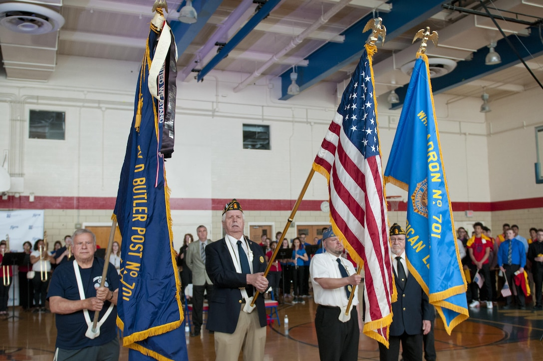 The American Legion Post 701, of White Oak, Pa., color guard presents the colors during the playing of the National Anthem during a ceremony for Staff Sgt. Michelle Satterfield in McKeesport, Pa., April 25, 2016. Satterfield is receiving a house built by the students of the McKeesport Area High School and Stephen Siller Tunnel to Towers Foundation for all of the volunteer work she has done in the past years. (U.S. Army photo by Staff Sgt. Dalton Smith / Released)