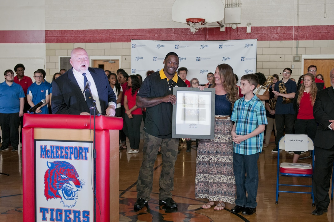 Arthur Moats, Pittsburgh Steelers linebacker, presents a collage of photos to Staff Sgt. Michelle Satterfield, with the 14th Quartermaster Detachment, during a ceremony for Satterfield in McKeesport, Pa., April 25, 2016. Satterfield is receiving a house built by the students of the McKeesport Area High School and Stephen Siller Tunnel to Towers Foundation for all of the volunteer work she has done in the past years. (U.S. Army photo by Staff Sgt. Dalton Smith / Released)