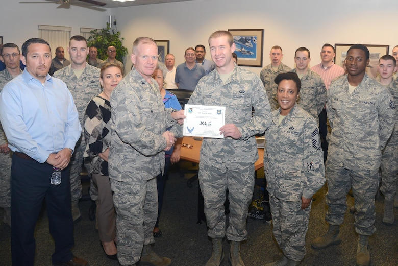 """Airman 1st Class Tyler Troge, 47th Contracting Flight contract specialist, accepts the """"XLer of the Week"""" award from Col. Darrell Judy, left, 47th Flying Training Wing vice commander, and Chief Master Sgt. Erica Shipp, right, 47th Mission Support Group superintendent, here, April 20, 2016. The XLer is a weekly award chosen by wing leadership and is presented to those who consistently make outstanding contributions to their unit and Laughlin. (U.S. Air Force photo by Airman 1st Class Brandon May)"""