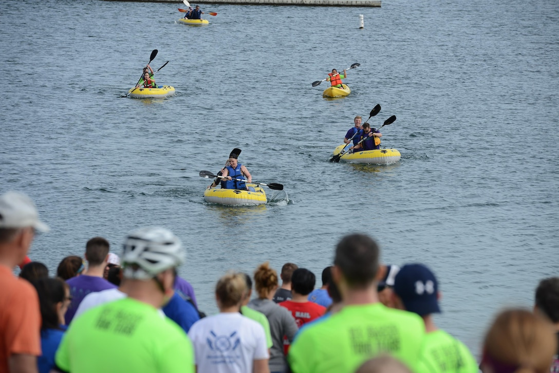 Onlookers watch Adventure Race XII participants finish the one-mile rafting portion of the race at Laughlin Southwinds Marina, Texas, April 23, 2016. Rafting was the final portion of the 28-mile race that was superseded by a 3-plus-mile run, six-foot tall wall climbs, a mud filled low-crawl, a concrete barrier hurdle and a 23- mile bike ride. (U.S. Air Force photo by Airman 1st Class Brandon May)