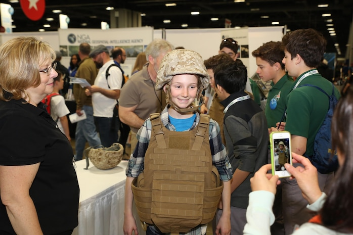 Kathy Halo (left), a safety engineer with Marine Corps Systems Command's Infantry Weapons Systems, watches as a young attendee tries on a Marine Corps helmet and protective vest during the USA Science & Engineering Festival April 14–17 in Washington, DC. This year marked MCSC's second year participating in the festival as part of an ongoing effort to partner with other government agencies, academic institutions and private industry to improve STEM education in the United States.  (U.S. Marine Corps photo by Mathuel Browne)