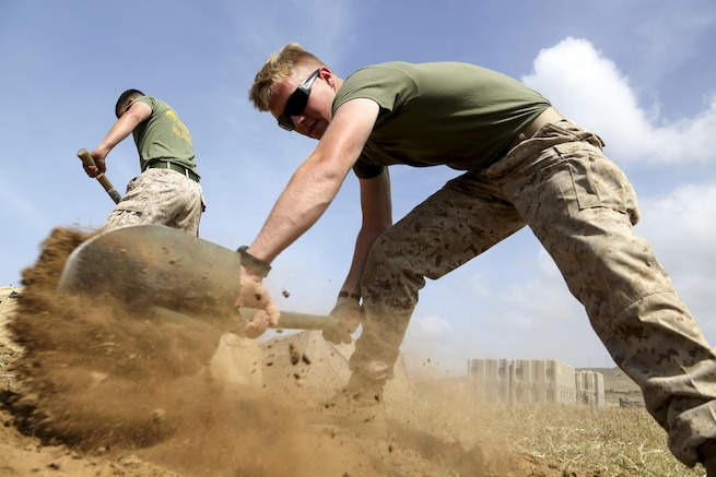 Marine Corps Lance Cpl. Seth A. Gordon digs a trench to conceal network cables as part of a Marine Expeditionary Unit exercise at Camp Pendleton, Calif., April 26, 2016. The exercise ensures communication and coordination among organic units. Marine Corps photo by Gunnery Sgt. Rome M. Lazarus
