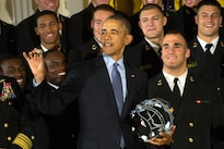 President Barack Obama holds a U.S. Naval Academy football helmet and inspects a team ring he received after awarding the Commander in Chief's Trophy to the team at the White House in Washington, D.C., April 27, 2016. DoD photo by EJ Hersom