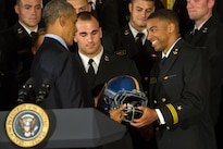 U.S. Naval Academy football team co-captain and college record-breaking quarterback Keenan Reynolds presents President Barack Obama with a team helmet during a Commander in Chief's Trophy award ceremony at the White House in Washington, D.C., April 27, 2016. The president presents the trophy to the Defense Department team with the most victories against its service rivals. DoD photo by EJ Hersom