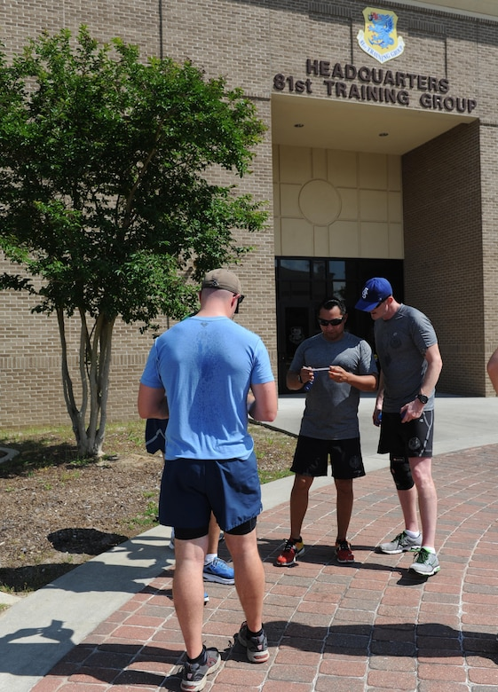 """GatorBulls"" team members work together to figure out a clue in front Matero Hall during the Wingman Week Heritage Hunt April 26, 2016, Keesler Air Force Base, Miss. The hunt, consisting of eight teams, was one of many events held throughout the week. The ""Training Group-A"" team was the winner of the event. (U.S. Air Force photo by Kemberly Groue)"