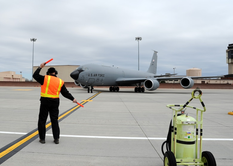 Dale Conner, 319th Operations Support Squadron aircraft server, directs a KC-135 Stratotanker April 26, 2016, on Grand Forks Air Force Base, N.D. The aircraft arrived from McConnell Air Force Base, Kan., as part of a severe weather evacuation. (U.S. Air Force photo by Airman 1st Class Ryan Sparks/Released)