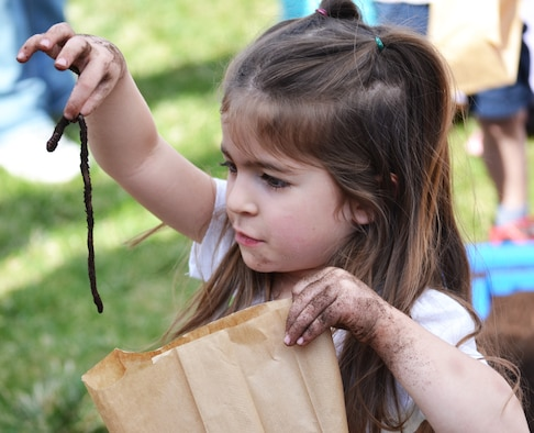 Madie Janaros puts a worm in her take home bag during the annual Earth Day event at Schriever Air Force Base, Colorado, Friday, April 22, 2016. Attendees were encouraged to take home the worms they dug out of a plastic pool filled with dirt in order to help fertilize their home gardens. (U.S. Air Force photo/Brian Hagberg)