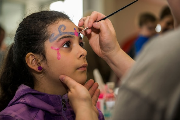 Jessica Kell, child of U.S. Air Force Staff Sgt. Luis Kell, a 52nd Logistics Readiness Squadron vehicle operations control center support NCO-in-charge, receives a face painting during the Spring Fling event in the Base Exchange at Spangdahlem Air Base, Germany, April 15, 2016. The Airman & Family Readiness Center hosted the event to raise awareness of the Exceptional Family Member Program and the service it provides for families. (U.S. Air Force photo by Airman 1st Class Timothy Kim/Released)