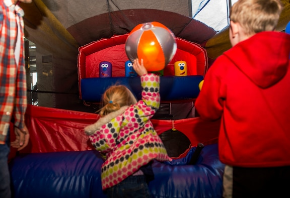 Keira Dell, child of U.S. Air Force Staff Sgt. Brady Dell, a 52nd Component Maintenance Squadron jet engine intermediate maintenance crew supervisor, tosses a beach ball in one of the stands during the Spring Fling event in the Base Exchange at Spangdahlem Air Base, Germany, April 15, 2016. The fair exposed families to the available resources and agencies available on base to aid special needs family members. (U.S. Air Force photo by Airman 1st Class Timothy Kim/Released)