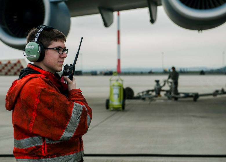 U.S. Air Force Senior Airman Hunter Stewart, a 726th Air Mobility Squadron instruments and flight control journeyman, talks into a two-way radio during a Boeing C-17 Globemaster III refuel on the flightline at Spangdahlem Air Base, Germany, April 22, 2016. The squadron emphasizes safe and secure communication to ensure aircraft can effectively carry out their mission. (U.S. Air Force photo by Airman 1st Class Timothy Kim/Released)