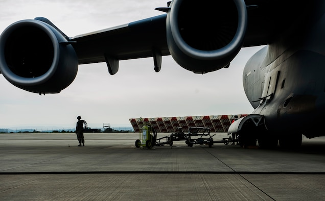An Airman assigned to the 726th Air Mobility Squadron coils a chord during a Boeing C-17 Globemaster III refuel on the flightline at Spangdahlem Air Base, Germany, April 22, 2016. The squadron supports passing heavy cargo aircraft through refueling, cargo and crew maintenance and other necessities required for mission success. (U.S. Air Force photo by Airman 1st Class Timothy Kim/Released)