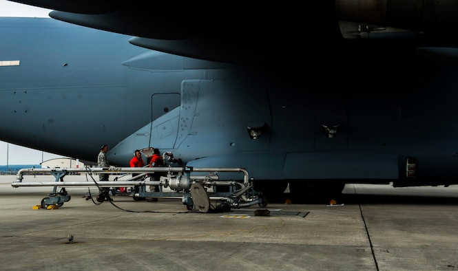 Two Airmen from the 726th Air Mobility Squadron begin to refuel a Boeing C-17 Globemaster III on the flightline at Spangdahlem Air Base, Germany, April 22, 2016. A strategic transit hub in Europe, the 726th AMS provides support for heavy cargo aircraft and aircrews passing through Spangdahlem, Germany. (U.S. Air Force photo by Airman 1st Class Timothy Kim/Released)