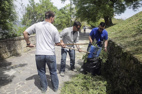 Marines with Special Purpose Marine Air-Ground Task Force Crisis Response-Africa Logistics Combat Element , clean up cut grass and garbage on a path at Castello di Lombardia in Enna, Sicily, during a community relations project on April 22, 2016.  Marines assist local areas in various projects to build relationships with the Sicilian government and people.  (U.S. Marine Corps photo by Cpl. Alexander Mitchell/released)