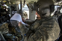 Army Staff Sgt. Paul Cimino reviews mission orders before taking off from Joint Base McGuire-Dix-Lakehurst and participating in an aerial gunnery training exercise over Warren Grove Gunnery Range, N.J., April 15, 2016. Cimino is a master gunner assigned to the New Jersey Army National Guard's 150th Assault Helicopter Battalion. Air National Guard photo by Master Sgt. Mark C. Olsen