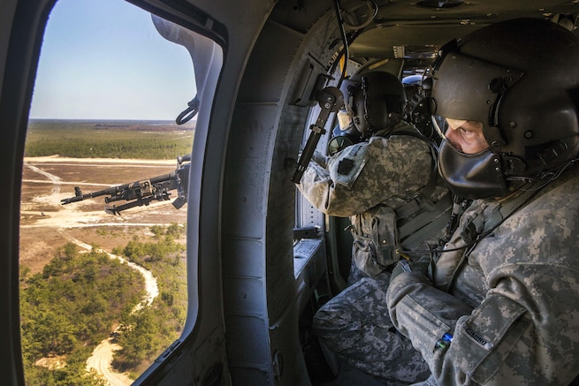 Army Staff Sgt. Paul Cimino, right, observes Army Sgt. William Harpe firing at targets with an M240B machine gun during an aerial gunnery training exercise over the Warren Grove Gunnery Range, N.J., April 15, 2016. Cimino is master gunner and Harpe is a crew chief assigned to the New Jersey Army National Guard's 150th Assault Helicopter Battalion. Air National Guard photo by Master Sgt. Mark C. Olsen