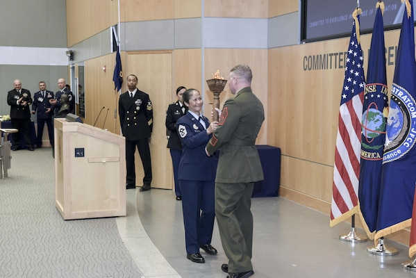 During the change of responsibility ceremony, CMSgt Arleen Heath passed the torch, which represents strength and leadership, to MGySgt Scott Stalker.
