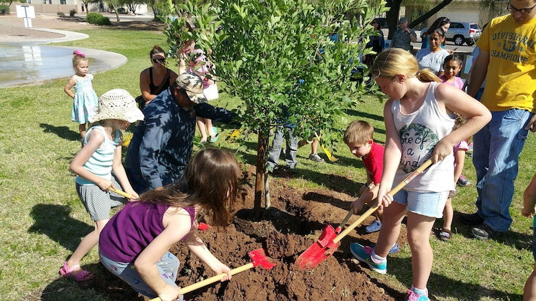 Children of Soaring Heights Communities plant an Ash tree at Davis-Monthan Air Force Base, Ariz., April 21, 2016. Soaring Heights celebrated Earth Day by inviting their residents to take part in planting a tree and learning about sustainability and conservation. (Courtesy photo)