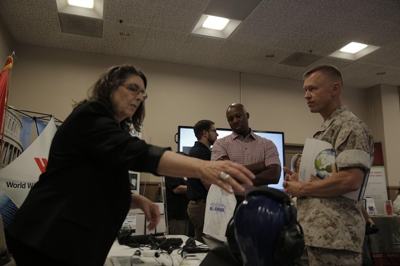 Jill DeVos, human resources, UmeVoice Inc., shows Lt. Col. Chris Dalton, academic department head, Marine Corps Logistics Operations Group, different communication equipment at the Officers' Club during the Tactical and Technology Day Expo April 19, 2016. (Official Marine Corps photo by Pfc. Dave Flores/Released)