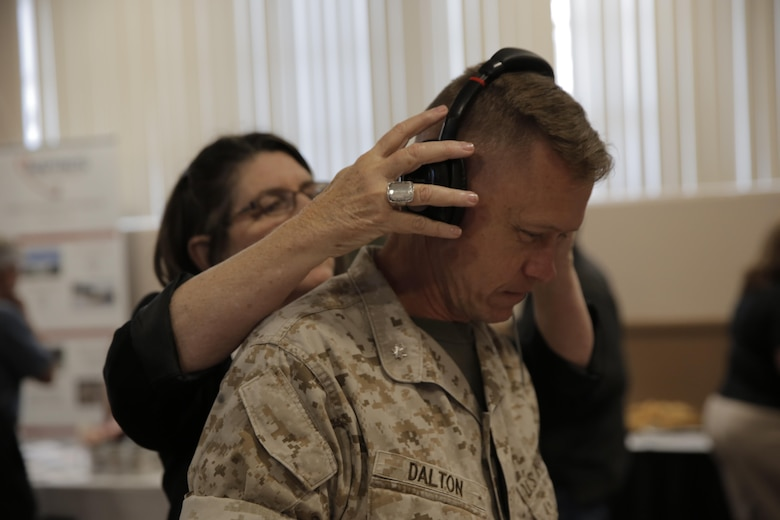 Lt. Col. Chris Dalton, academic department head, Marine Corps Logistics Operations Group, listens to theBoom, a microphone designed for clear audio even with loud background noise, at the Officers' Club during the Tactical and Technology Day Expo April 19, 2016. (Official Marine Corps photo by Pfc. Dave Flores/Released)