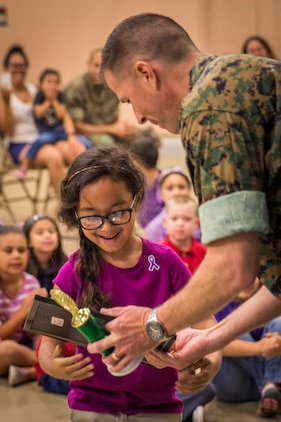 Lt. Col Sean Henrickson presents a student with an award during an Earth Day assembly at Middleton S. Elliott Elementary School aboard Laurel Bay April 22. Students drew Earth Day related artwork for a competition judged by the recycling department aboard Marine Corps Air Station Beaufort. Henrickson is the executive officer of MCAS Beaufort.